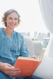 Blonde woman sitting on her couch reading a book Royalty Free Stock Image