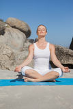 Blonde woman sitting in lotus pose on beach on mat Royalty Free Stock Photo