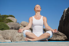Blonde woman sitting in lotus pose on beach on mat Stock Image