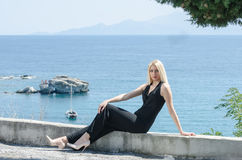 Blonde woman sitting on low wall ocean as background Royalty Free Stock Photography