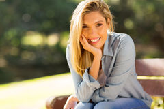 Blonde woman sitting outdoors Royalty Free Stock Image