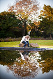 Blonde woman sitting on rock under oak Stock Photography