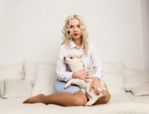 Blonde woman sitting on a sofa with puppy husky dog. girl playing with a dog Royalty Free Stock Image