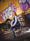 Blonde woman sitting on stairs against cabin with graffiti Royalty Free Stock Photos