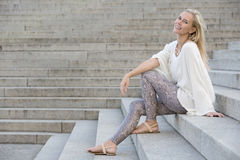 Blonde woman sitting on stairs Stock Image
