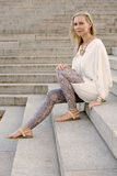 Blonde woman sitting on stairs Stock Photography