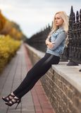 Blonde woman sitting at the stone fence. In autumn park Royalty Free Stock Photography