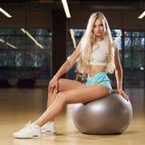 Blonde woman sitting on swiss ball Stock Photo