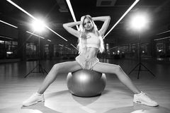 Blonde woman sitting on swiss ball. Pretty slim blonde woman with long hair, dressed in white crop top, blue shorts and trainers, sitting on silver exercise ball Stock Photo