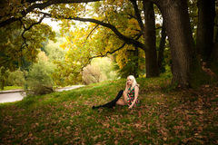 Blonde woman sitting under big tree at autumn park Stock Images