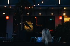 Blonde Woman Sitting Under String Lights at Night Stock Images