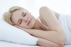Woman peacefully sleeping on a soft white bed. royalty free stock image