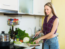 Blonde woman slicing green pepper Royalty Free Stock Images