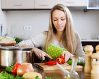 Blonde woman slicing red pepper Royalty Free Stock Photo