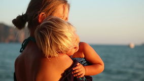 Blonde woman with small child admires sea sunset. Young blonde longhaired woman with small child in hands admires sea sunset stock video footage