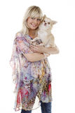 Blonde woman with small dog on the arm. Blonde woman smiling with small chihuahua dog on her arm Royalty Free Stock Image