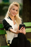 Blonde woman with smart phone on a bench in park Stock Photography
