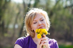 Blonde woman smell dandelion outdoor Royalty Free Stock Photos