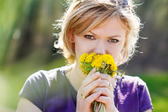 Blonde woman smell dandelion Stock Image