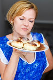 Blonde woman smell and holding tarts with jam on plate Stock Image