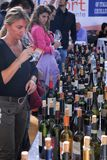 Blonde woman smell wine from her glass at food fair Turin Italy Royalty Free Stock Photos