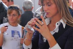 Blonde woman smell wine from her glass at food fair Turin Italy Stock Images