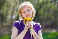 Blonde woman smelling dandelion Royalty Free Stock Photography