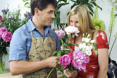 Blonde woman smelling flowers in flower shop, male florist looking on, smiling, side view Stock Photos