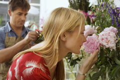 Blonde woman smelling flowers in flower shop, male florist working in background, side view Royalty Free Stock Photography
