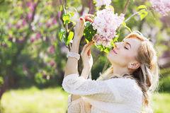 Blonde woman smelling a lilac. Beautiful woman in a spring garden with blooming lilacs Stock Photo