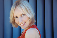 Blonde woman smiling, dressed in red sportwear. Day, outdoor stock photo
