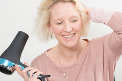 Blonde Woman Smiling While Drying Her Hair Using Blow Dryer royalty free stock images