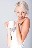 Blonde woman smiling holding a cup royalty free stock photography