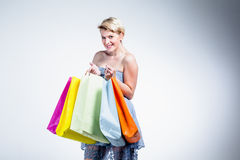 Blonde woman smiling and holding paper bags Royalty Free Stock Photos