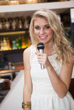 Blonde woman smiling while singing into a microphone Stock Image