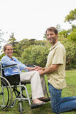 Blonde woman smiling in wheelchair with partner kneeling beside Stock Photos