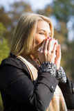 Blonde woman sneezing in tissue Stock Photo