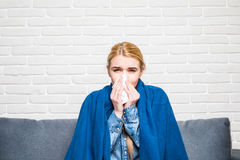 Blonde woman sneezing in a tissue on sofa in the living room. Blonde sneezing in a tissue in the living room Stock Photography