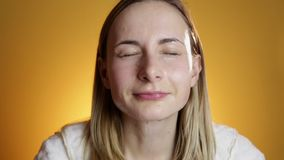 Blonde woman splashing her face against a on a yellow background stock footage