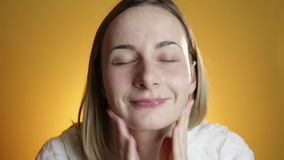 Blonde woman splashing her face against a on a yellow background stock video