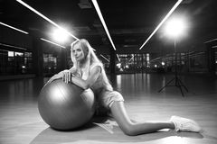 Blonde woman in sports clothing posing with silver yoga ball. Gorgeous blonde female model, dressed in crop top, blue shorts and white trainers, sitting on Stock Images