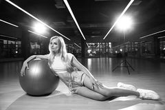 Blonde woman in sports clothing posing with silver yoga ball. Gorgeous blonde female model, dressed in crop top, blue shorts and white trainers, sitting on Royalty Free Stock Photos
