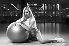 Blonde woman in sports clothing posing with silver yoga ball. Gorgeous blonde female model, dressed in crop top, blue shorts and white trainers, sitting on Stock Photo