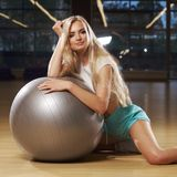 Blonde woman in sports clothing posing with silver yoga ball Royalty Free Stock Photos