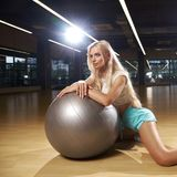 Blonde woman in sports clothing posing with silver yoga ball Royalty Free Stock Photography