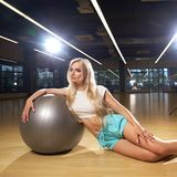 Blonde woman in sports clothing posing with silver yoga ball Stock Photo