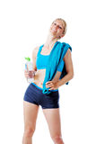 Blonde woman in sports wear satisfied with her performance holding a water bottle and blue towel Stock Photo