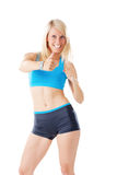 Blonde woman in sports wear showing thumbs up and smiling Stock Photography