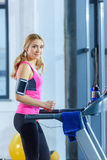 Blonde woman in sportswear training on treadmill and smiling at camera Stock Image