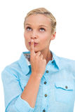 Blonde woman standing with her finger on her lips Stock Image